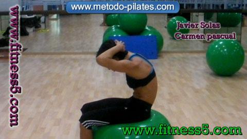 Ejercicio pilates Flexion de la columna con las manos en la cabeza y encima de la pelota