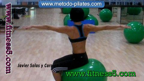 Ejercicio pilates Rotaciones de la columna con la cadera fija encima de la pelota y los brazos en cruz