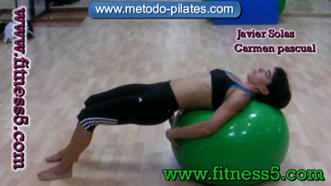 Ejercicio pilates Extender las piernas y tumbarse en la pelota hacia atras.